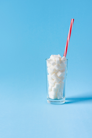 A glass full of sugar cubes with straw isolated on blue background. Unhealthy diet concept. Copy space