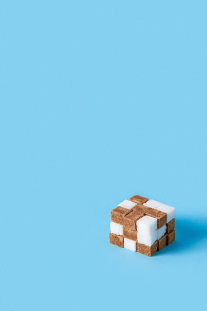 cube made of white and brown sugar cubes isolated on blue background. Copy space Stock Photo