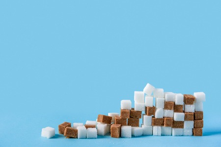 ruined wall made of white and brown sugar cubes isolated on blue background. Copy space Stock Photo