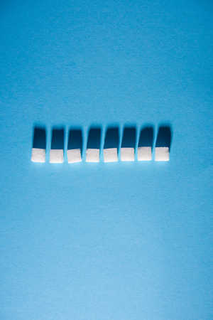 White sugar cubes arranged in horizontal line on blue background. Isolated. Copy space. Top view. Hard shadows Stock Photo