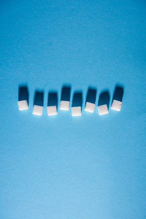 uneven horizontal line arranged of white sugar cubes on blue background. Isolated. Copy space. Top view. Hard shadows