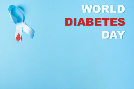 inscription world diabetes day and the blue ribbon awareness with red blood drop on a blue background. World diabetes day,14 november. Copy space. Top view Stock Photo