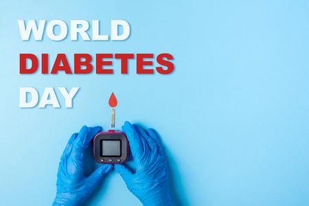 inscripción día mundial de la diabetes y enfermera haciendo un análisis de sangre con gota de sangre roja con tira reactiva de glucosa en sangre y medidor de glucosa. Copie el espacio. Vista superior Foto de archivo