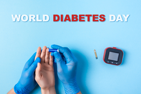inscription world diabetes day and Nurse making a blood test with lancet. Man's hand with red blood drop with Blood glucose test strip and Glucose meter. Copy space. Top view