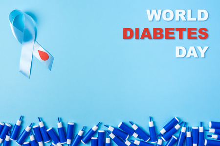 inscription world diabetes day blue ribbon awareness with red blood drop and line of lancets on a blue background. World diabetes day,14 november. Copy space. Top view Stock Photo
