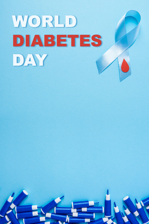 inscription world diabetes day and blue ribbon awareness with red blood drop and line of lancets on a blue background. World diabetes day,14 november. Copy space. Top view