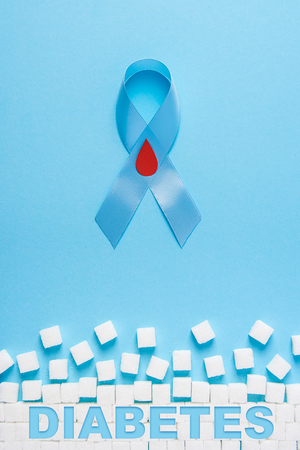 inscription diabetes the blue ribbon awareness with red blood drop and ruiden wall made of white sugar cubes on a blue background, world diabetes day Stock Photo