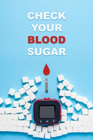 inscription check your blood sugar and red blood drop and wall made of sugar cubes ruined by Blood glucose test strips and Glucose meter on blue background, world diabetes day. Copy space. Top view