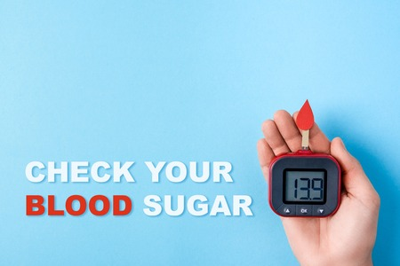 inscription check your blood sugar and red blood drop with Blood glucose test strips and Glucose meter in man hand on blue background, world diabetes day. Copy space. Top view