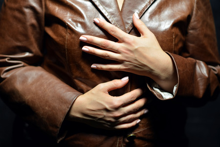 leather coat: Hands of a woman in a brown leather coat. Hands clasped together. Beautiful manicure.