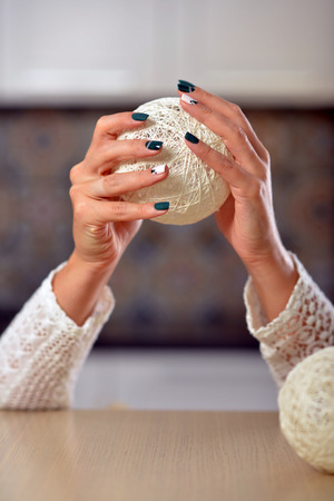 Female hands with manicure holding hands knitted balls. Stock Photo