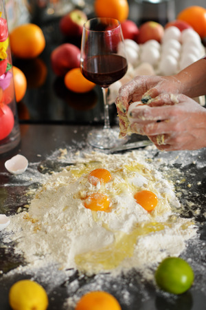 worktops: Kitchen. On the table lies a lot of brightly colored fruit, clear vase with pouting balls. Womens hands are in the process of breaking the eggs into the flour.
