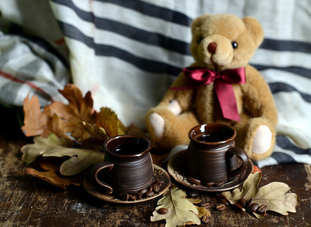 Autumn Still Life. Brown ceramic coffee cups. Bunch rowan and yellowed leaves. Knitted scarf. Coffee beans. Teddy Bear sitting near to coffee cup.