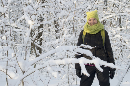 among: girl in a green cap is among the snow-covered trees