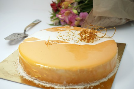 frosting': cake with orange frosting and caramel, flowers on background