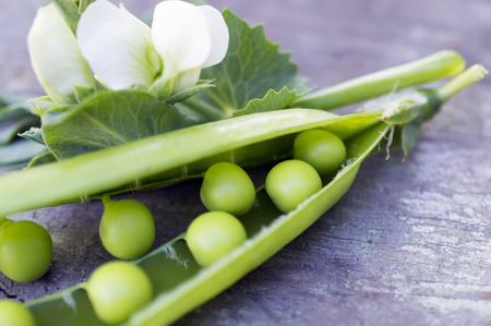pods of green peas on wooden background Stock Photo