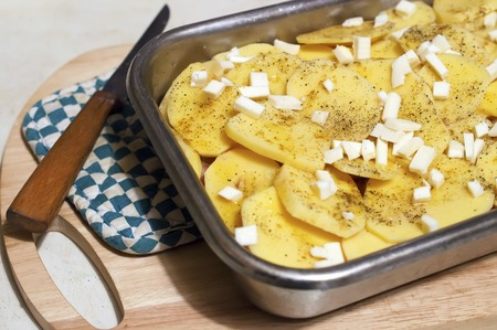 metalic: sliced potatoes and cheese in a baking dish, knife and potholder on a cutting board Stock Photo