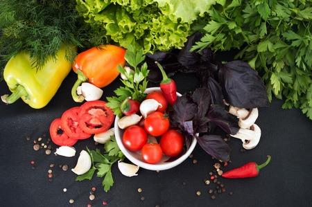 Verse greens, kruiden en groenten op een zwarte achtergrond. Gezond eten. Groenten, bovenaanzicht Stockfoto