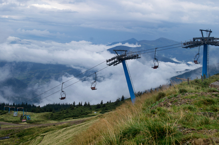 Chairlift in mountains on summer against the background of green Stock Photo