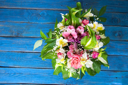 bright bouquet of alstroemeria, roses and greens on blue backgr Stock Photo