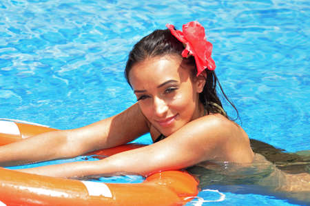 Young woman swimming in a pool with a lifebuoy photo