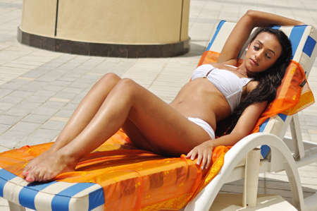 Young beautiful woman tanning on the sun lounger photo