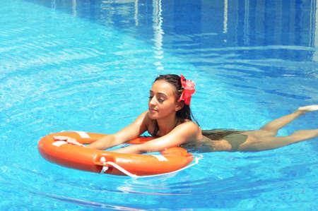 Beautiful woman tanning in a swimming pool photo