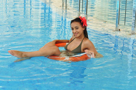 Beautiful woman sitting in a lifebuoy in a swimming pool  photo