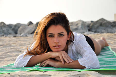 beach towel: Beautiful woman laying on beach towel at sunset Stock Photo