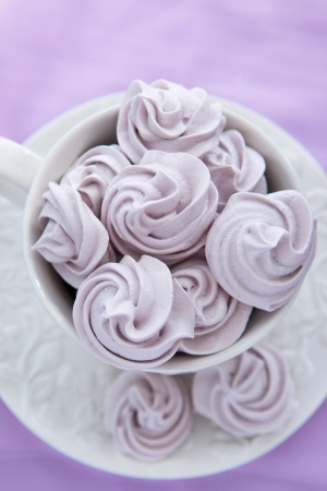 Meringues in a white teacup on a lilac color background photo