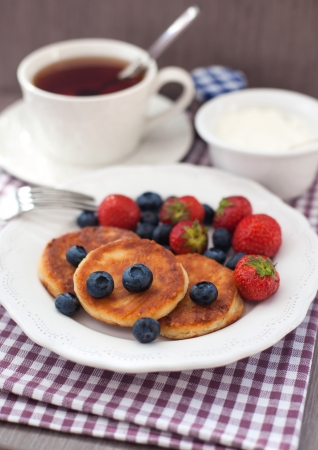 Cheese pancakes (syrniki) with fresh blueberry and strawberry on the white plate with cup of tea on the background