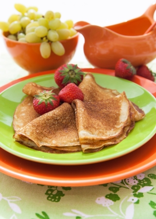 blini: Fresh pancakes (blini) with strawberries on colorful dish