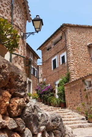 Narrow street old traditional houses village with flowers, Fornalutx, Majorca island