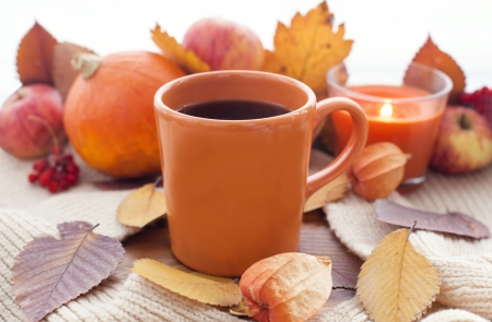 Orange coffee cup on the autumn fall leaves and candle with fruits on the background 스톡 콘텐츠