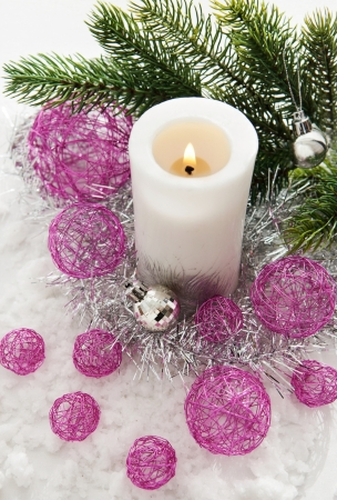 White candle and Christmas decorations around photo