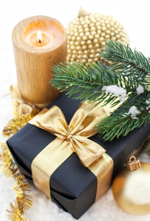 Golden Christmas composition with gift box, candle and branch of spruce Stock Photo - 23051525