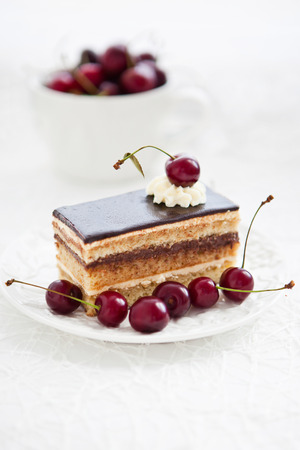 Portion of Opera cake decorated with fresh cherry photo