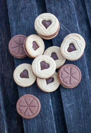 Heart shaped cut out cookies with chocolate filling on the wooden table Stock Photo