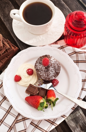 Chocolate muffin served on a plate with fresh berries and cream photo