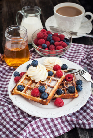 Breakfast with belgian waffles decorated with whipped cream and fresh berries photo