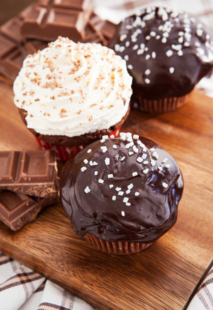Chocolate cupcakes decorated with glaze and cream on wooden board photo