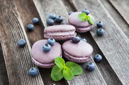 Violet french macarons with blueberry and mint on wooden table 스톡 콘텐츠