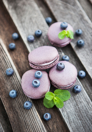 Violet french macarons with blueberry and mint on wooden table Archivio Fotografico