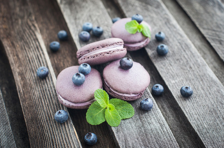 Violet french macarons with blueberry and mint on wooden table photo