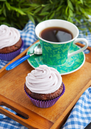 Cupcake and cup of coffee on the tray photo