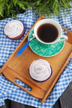 Cupcakes and cup of coffee on the tray, top view photo