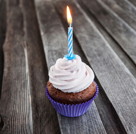 Tasty birthday cupcake with candle on wooden table
