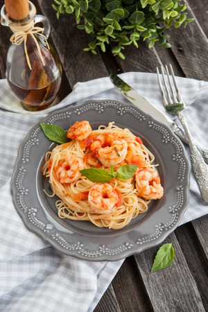 Plate of fresh spaghetti with prawns and tomatoes on wooden table