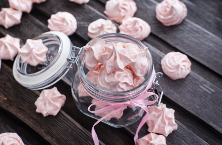 Pink meringues in a glass jar on wooden table photo