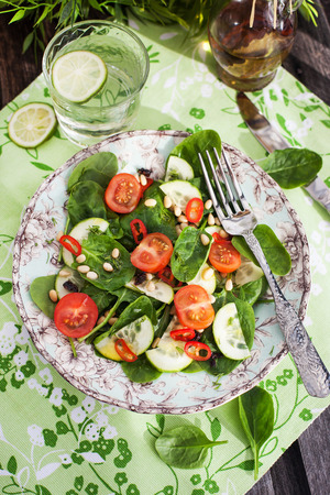 Healthy fresh salad with spinach, tomato, cucumber and pine nuts, top view photo
